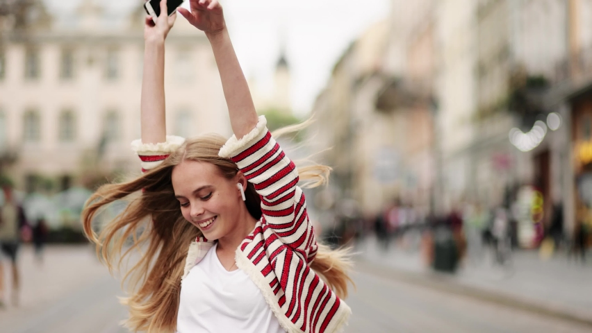 Young adult happy woman dancing in downtown very emotional. Slow motion of happy young woman in wireless headphones dancing singing outdoors in city street having fun alone.