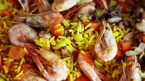 Cooking Spanish paella dish with rice in close up video clip.Delicious Mediterranean cuisine being cooked in royalty free footage