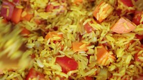 Cooking Spanish paella dish with rice on hot pan in close up video clip.Royalty free footage of traditional Mediterranean cuisine being cooked in closeup
