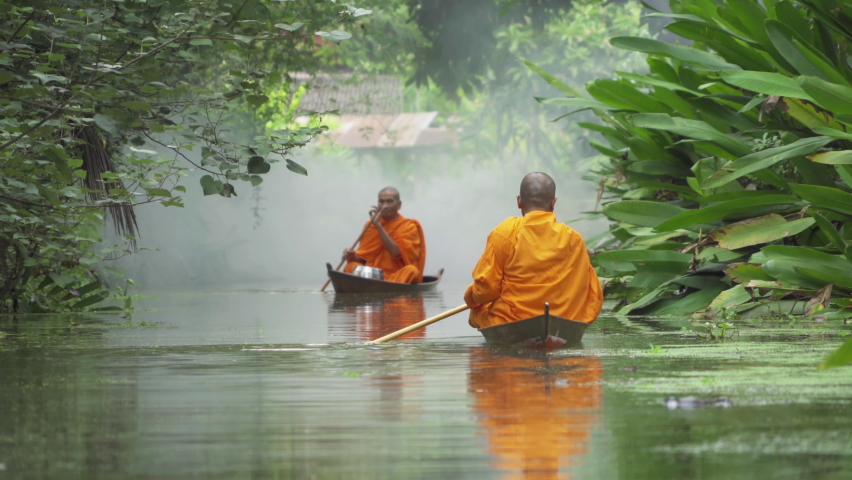 Local Thai monks with alms. Men sailing wooden boat in canal or river for receiving food, Traditional Thai Buddhism lifestyle. Asia, Thailand.  Royalty-Free Stock Footage #1061824513