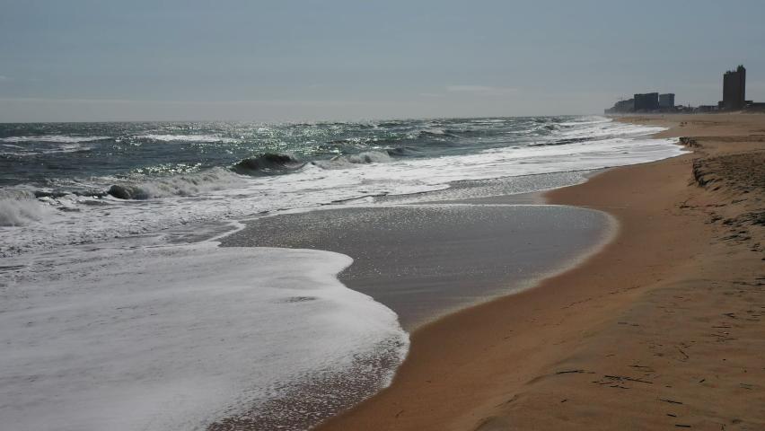 Shoreline at Virginia Beach, Virginia. Drone flying straight, then rising.