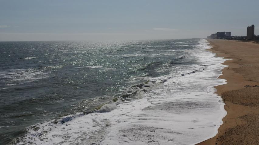 Drone descend on ocean shoreline in Virginia Beach, Virginia.