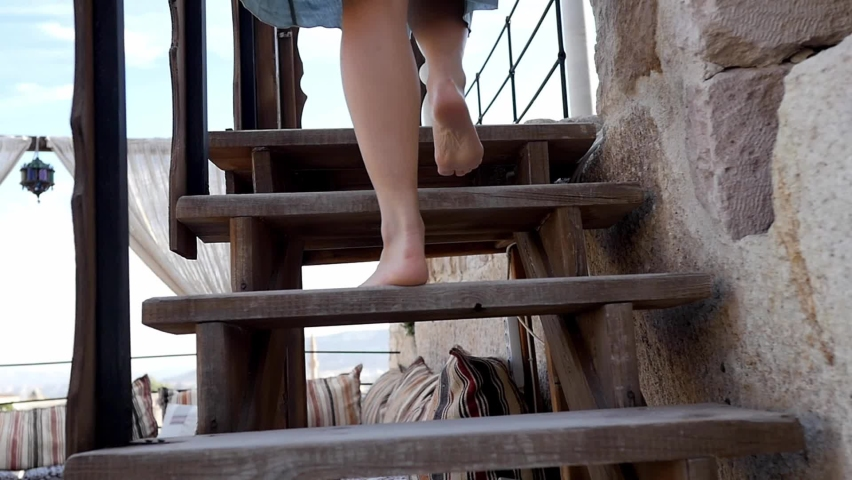 Legs of a pretty girl walking up the ancient stairs while relaxing on a warm summer day. Bare feet of a woman in a light dress climbing stairs. A tourist, resting, goes up the steps in the street