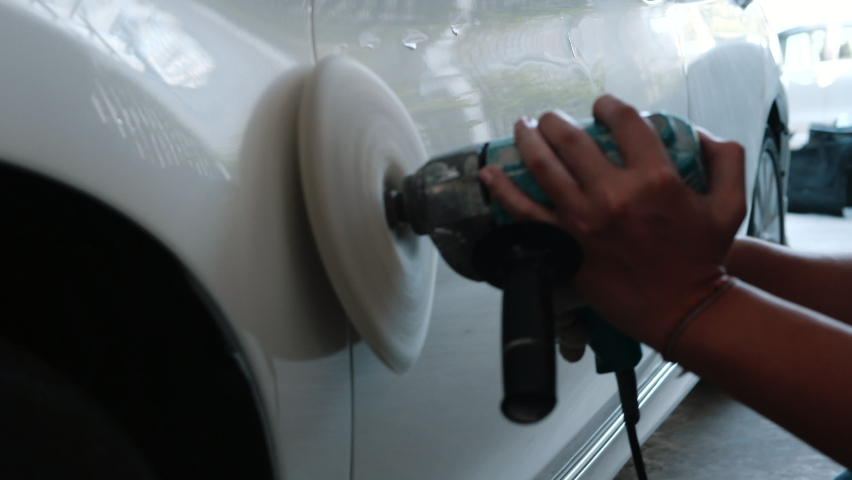 White car body polishing with polisher tool in auto service. Waxing car after car wash. Car body work - 4K
