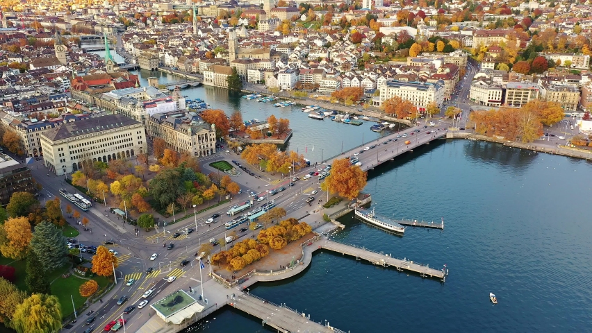 Aerial footage of the Zurich old town where the Limmat river joins lake Zurich with tramway running on a bridge in Switzerland largest city.