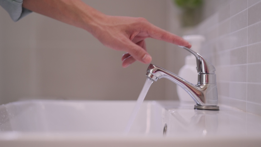 The faucet in the bathroom with running water. Man keeps turning off the water to save water energy and protect the environment.