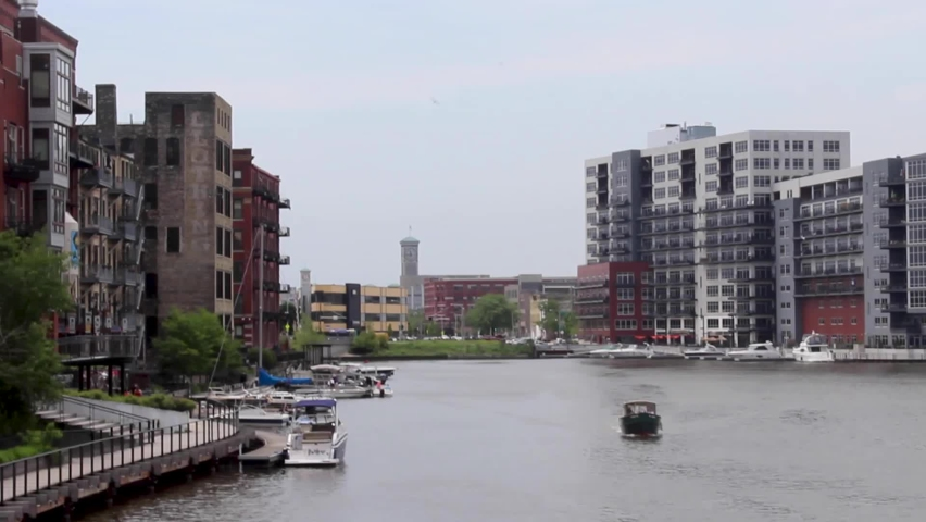 Boat driving down the Milwaukee river surrounded by residential and office buildings in Milwaukee, Wisconsin
