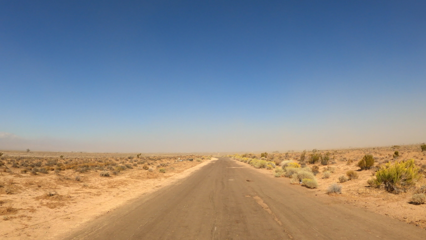 Driving down a desolate Mojave Desert road covered with sand by wind and storms - point of view