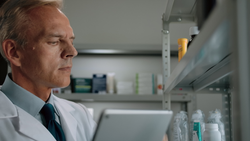 A close-up of a man pharmacist in a robe, shirt and tie conducts an audits medicine goods in drugstore. A mature caucasian male, owner of a pharmaceutical small business, engaged in reconciliation. Royalty-Free Stock Footage #1061843932