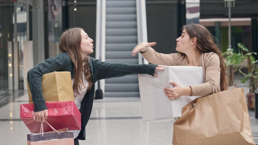 Two Attractive Woman is Fighting For Shopping. Shopaholics are Fighting for Purchases.Fashionistas are Fighting for Purchases. Two Beautiful Girls with Bags in Hands are Arguing in the Store