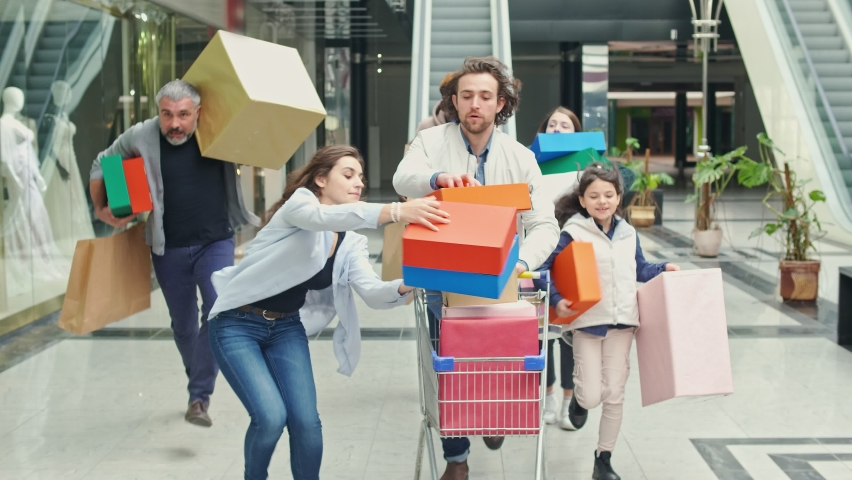 Group of Shopaholics With Shopping Bags Running Along Mall Hurrying to Make Purchases on Black Friday. Running to Be First In-Store. Crazy Shopping at Big Sales. Royalty-Free Stock Footage #1061845138