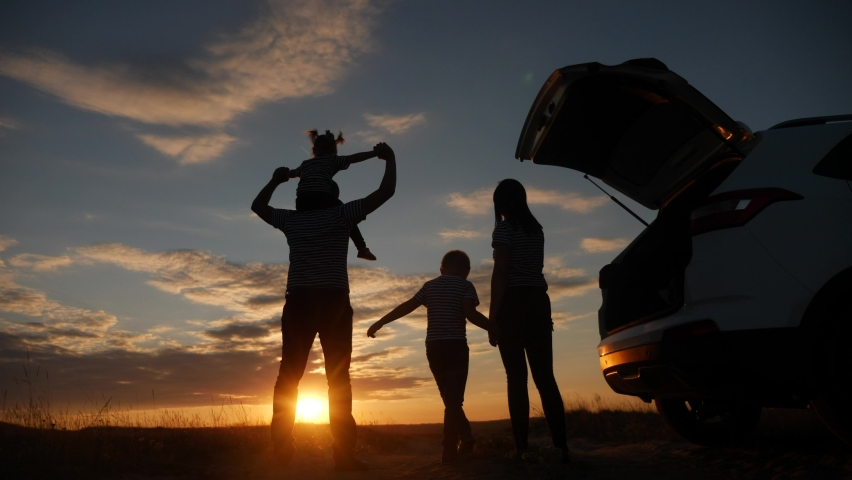 Happy family children kid together standing next to car watching the sunset silhouette in park. family travel dream concept. happy family stand with sunlight their backs journey watching in the park