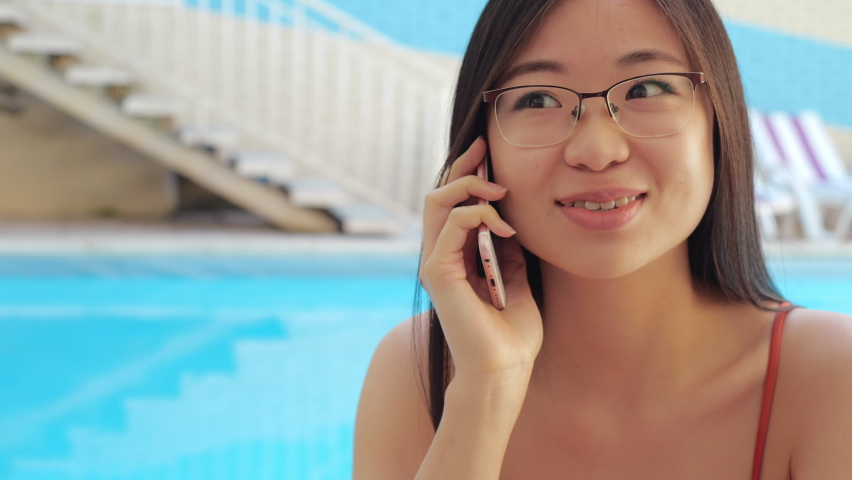 Focused frowning Asian millennial businesswoman speaks on smart phone, solves business problems sitting in pool in spa complex or communicates with friends with mobile network technology, closeup