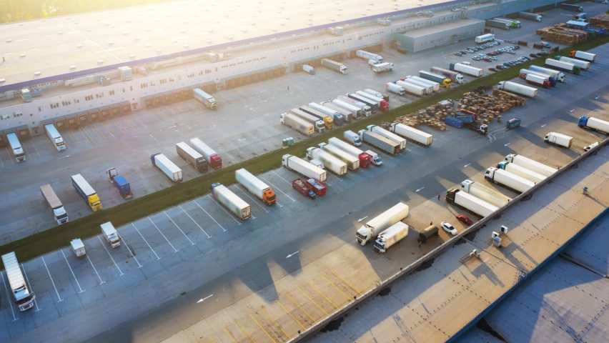 Logistics park with a warehouse and loading hub. Semi-trucks with cargo trailers standing at the ramps for loading/unloading goods at sunset. Aerial hyper lapse. Royalty-Free Stock Footage #1061864923