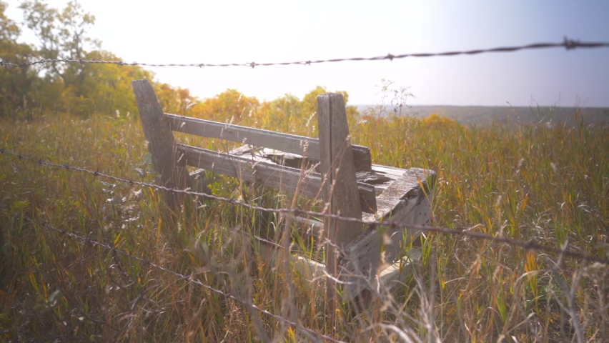 Old wooden bench behind barbed wire fence