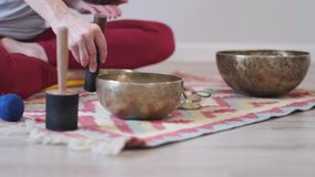 Woman playing on Tibetan singing bowl while sitting on yoga mat. Vintage tonned. stock footage. Slow Motion video. Close up