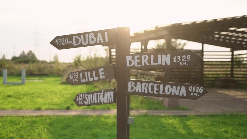 Old wooden road sign arrows with directions - Dubai, Berlin, Lille, Barcelona, Stuttgart at sunset