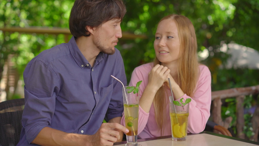 In a cafe young couple have a chat. They drink their drinks using reusabla steel straws. Concept of reducing the use single plastic Royalty-Free Stock Footage #1061899510