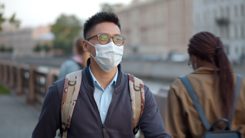Portrait of asian man wearing safety mask walking in city. Young korean student with backpack in protective mask going to classes by riverside in city center Royalty-Free Stock Footage #1061900857