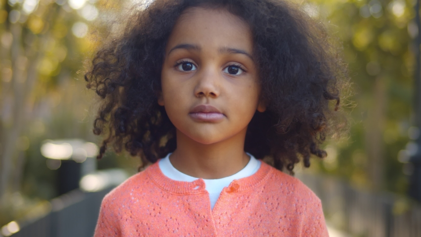 Close up portrait of serious little african girl looking at camera. Portrait of adorable preschool afro-american kid standing in ark over blurred background