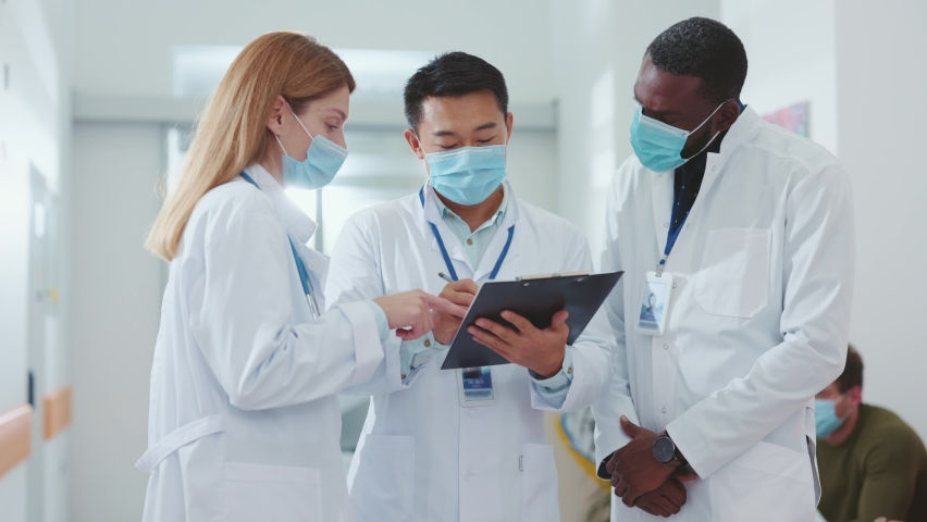Business team of healthcare multi-ethnic workers wearing face masks discussing coronavirus outbreak virus infection pandemic negotiating in the hospital. Quarantine. Royalty-Free Stock Footage #1061905708