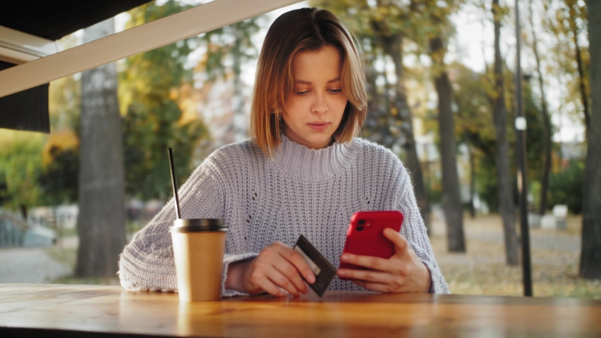 Smiling young customer holding credit card and smartphone sitting in the street cafe . Happy female shopper using instant easy mobile payments making purchase in online store Royalty-Free Stock Footage #1061907232