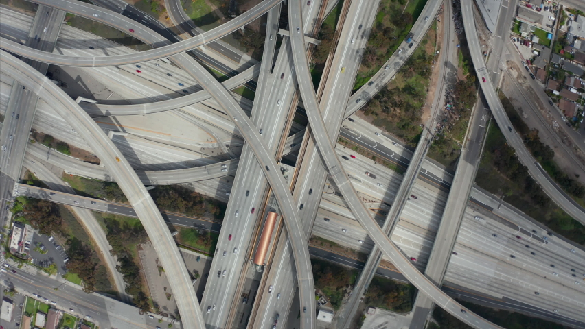 AERIAL: Spectacular Turning Overhead Shot of Judge Pregerson Highway showing multiple Roads, Bridges, Viaducts with little car traffic in Los Angeles, California on Beautiful Sunny Day  Royalty-Free Stock Footage #1061911675