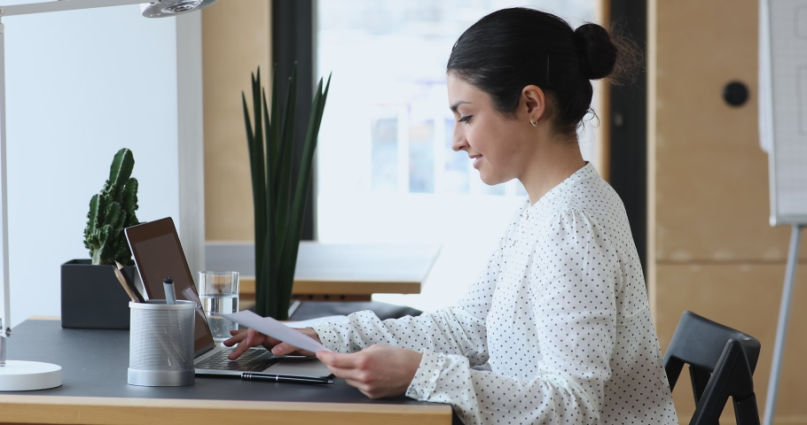 Side view focused indian ethnicity young woman holding paper documents, working on computer in modern office. Concentrated smart mixed race professional analyzing financial or marketing report. Royalty-Free Stock Footage #1061923087