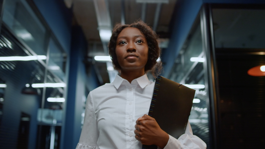 Portrait of focused businesswoman walking on meeting in office corridor. Closeup african american woman walking in corridor. Serious afro business woman going with folder in business center hallway. Royalty-Free Stock Footage #1061926930