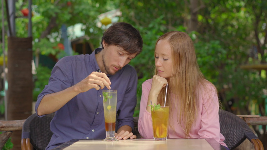 In a cafe young couple have a chat. They drink their drinks using reusabla steel straws. Concept of reducing the use single plastic Royalty-Free Stock Footage #1061928430