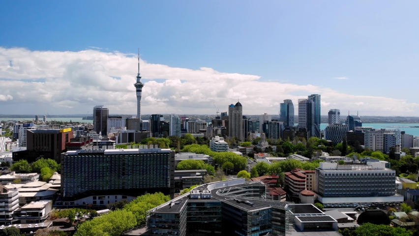 Auckland City and Sky Tower aerial birds eye view. Summer sunny day. Beautiful cityscape of skyscrapers, business and university buildings and parks, New Zealand