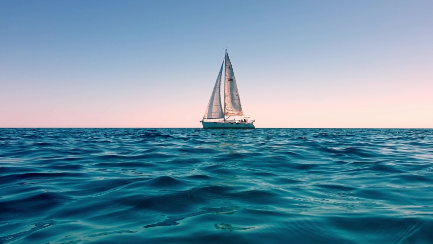 Low-angle sea-level view of small yacht boat sailing in calm open sea at sunset