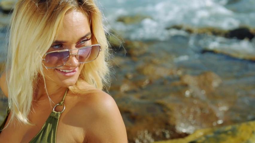 Blonde haired model girl in bikini standing by the sea turns her head.