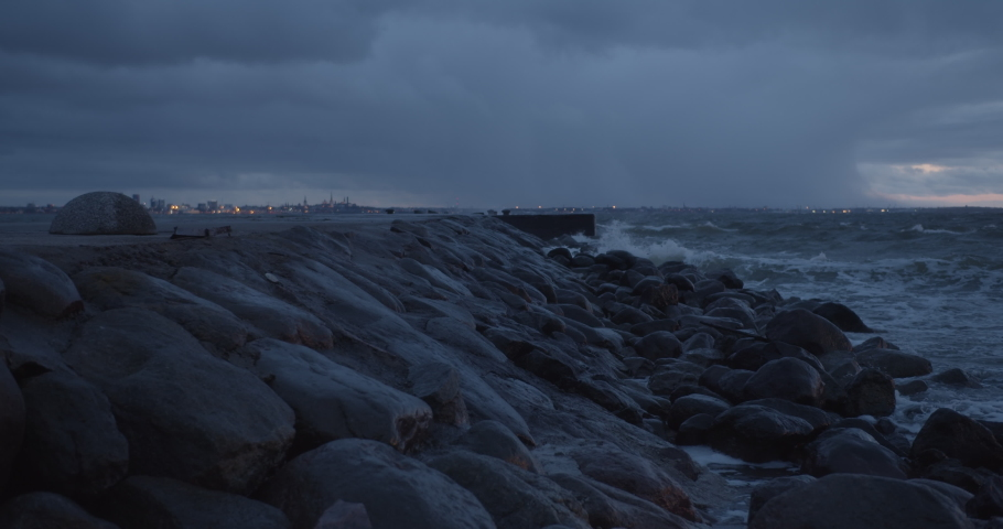 Storm waves crashing to the pier rocks in dark windy evening slow motion