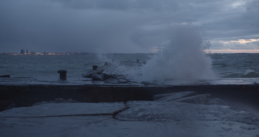 Windy stormy weather big and powerful waves hitting the pier
