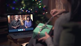 Family celebrating Christmas through a Video call. Parents online celebrating with family during X-mas holidays. Opening presents. Coronavirus celebrations maintaining the distance.