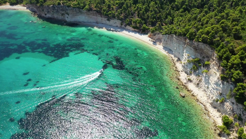 Aerial drone video of tropical paradise exotic island covered in pine trees with turquoise crystal clear beach in Caribbean destination