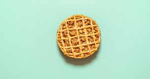 Apple pie with lattice crust in slices moving on a green seamless background. Apple pie funny stop motion. Animated home-baked apple dessert 4k video