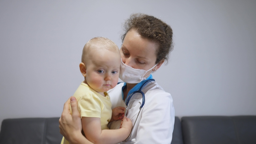 Nurse in face cover cuddling sad baby in arms to calm down and ease stress. Frontline healthcare workers help families during coronavirus threat Royalty-Free Stock Footage #1061955544