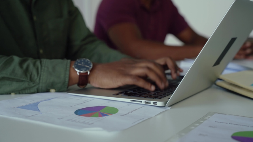 Male accountant checking pie charts logging in figures onto spreadsheet on laptop sitting in conference room | Shutterstock HD Video #1061961907
