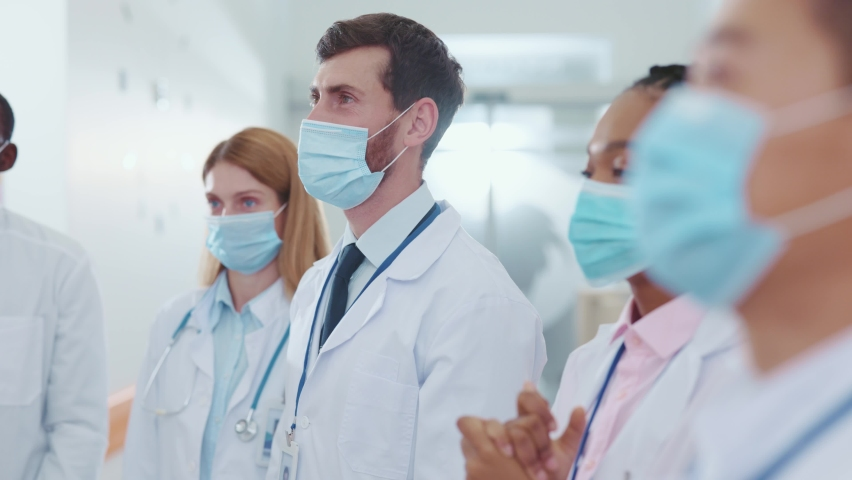 Multi-race professional medical doctors and assistants wearing protective masks against coronavirus applauding on team conference business employment meeting in corridor. Cooperation and success. Royalty-Free Stock Footage #1061963998