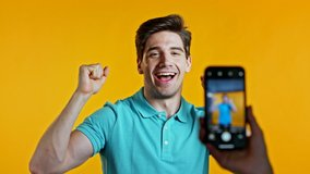 Smiling vlogger man recording video of hisself dancing in front of smartphone camera on yellow background. Influencer makes funny social media clip