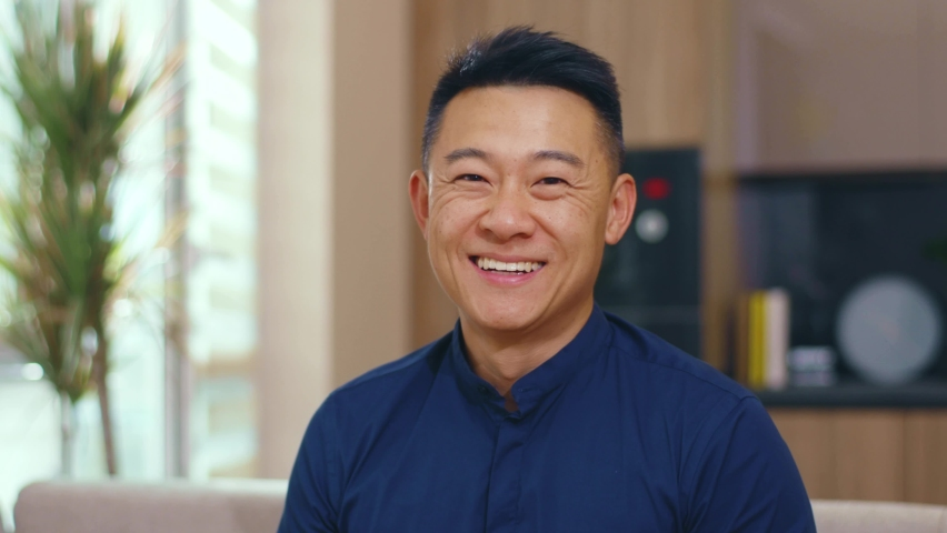 Smiling asian chinese man look at camera happy at home. Feel confident. Young japanese korean discussion casual relax face communication. Slow motion