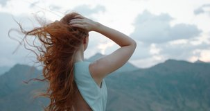 Carefree girl with red hair raising her hands up to the wind, embracing freedom and tranquility, enjoying scenic view of mountains 4k footage