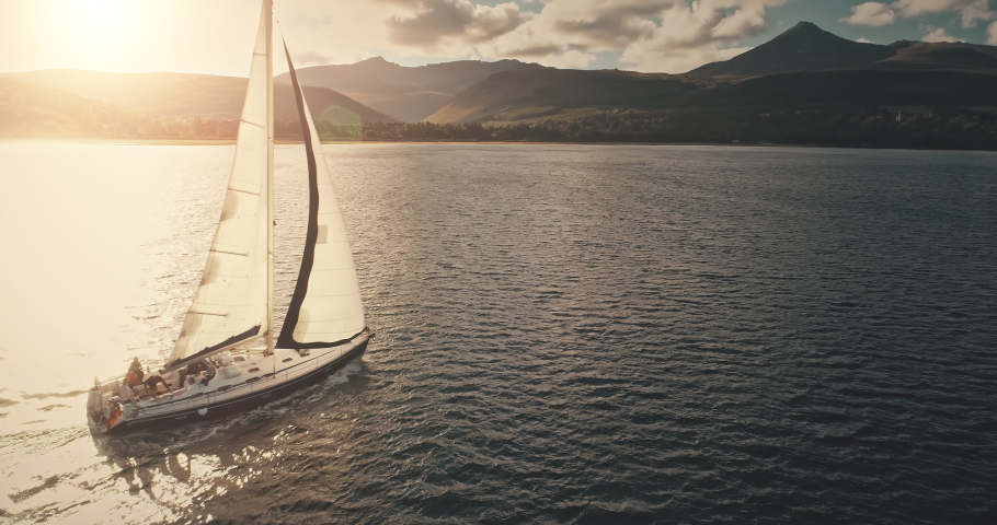 Sun reflection at sailboat on ocean bay aerial. Summer sea cruise on ship at green mountains island of Arran on yachts with passengers. Scotland sea coast water with vessel. Cinematic drone shot Royalty-Free Stock Footage #1061971159
