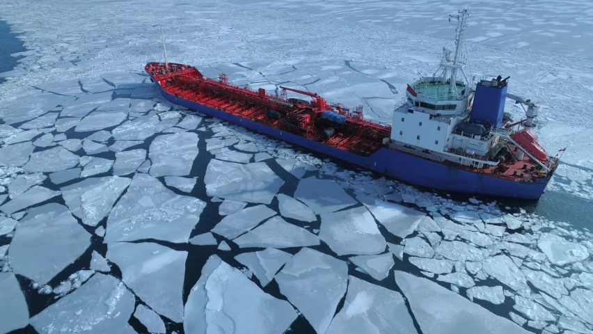 Aerial above epic huge steel icebreaker breaks ice by bow of ship and floats in large sea ice floes. Maintaining navigation in a frozen sea channel laying. Self-propelled specialized vessel red ship | Shutterstock HD Video #1061971969