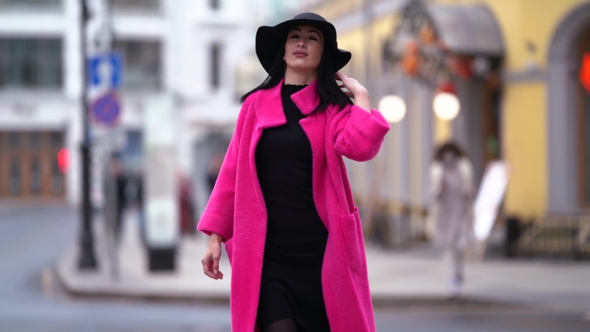 A stylish black-haired woman in a pink coat and black hat walks and poses on a blurry city street background. | Shutterstock HD Video #1061973688