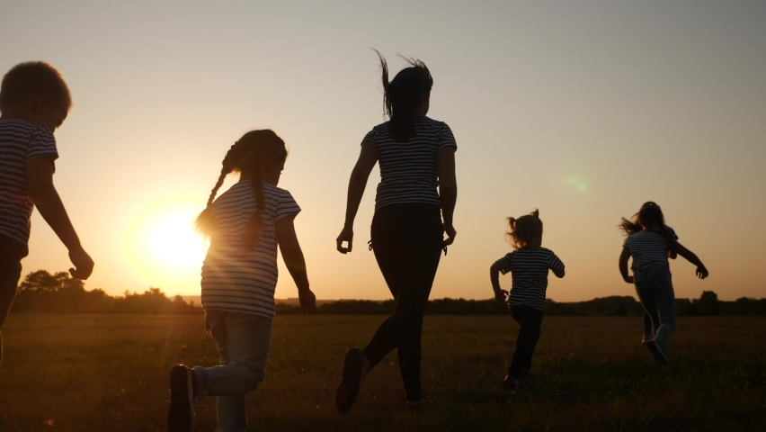 children happy family kid together run in the park at sunset silhouette. people in the park concept. mom daughter and son joyful run. happy family and little baby child summer fun kid dream concept Royalty-Free Stock Footage #1061987146
