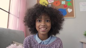 Happy cute small african kid girl vlogger talking to camera at home recording vlog for social media blog, video conference calling virtual friend having online meeting sitting on couch, web cam view.