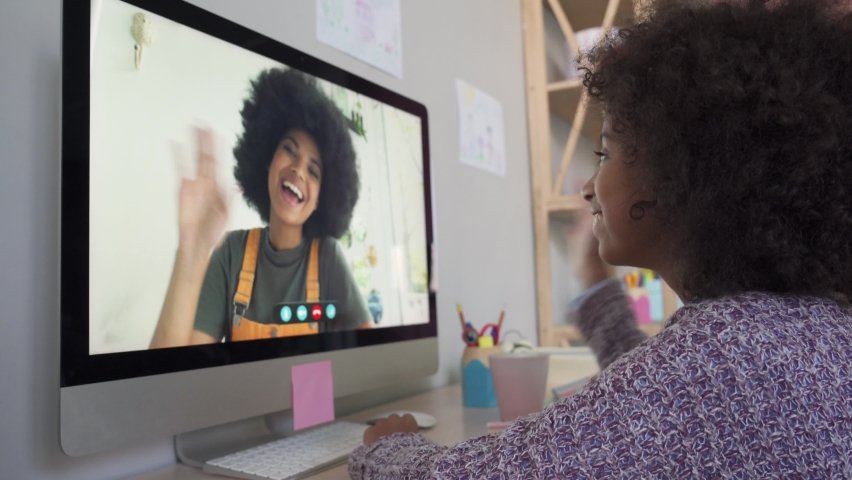 Cute funny african kid girl talking to friend, sister, mom or distance teacher during online virtual family chat videocall meeting by video conference call using pc computer sitting at home desk. Royalty-Free Stock Footage #1062010282